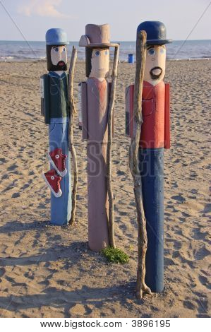 Three Wood Figures On Beach