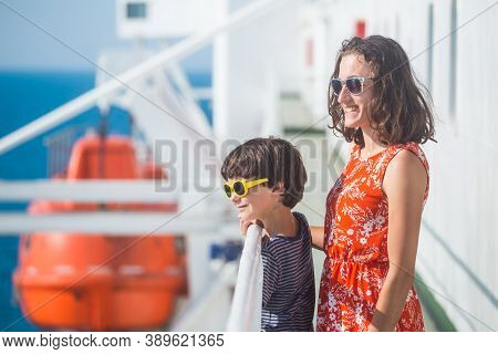 A Woman Is Sailing On A Cruise Ship With Her Child, A Girl Is Standing At The Fence On The Ship And