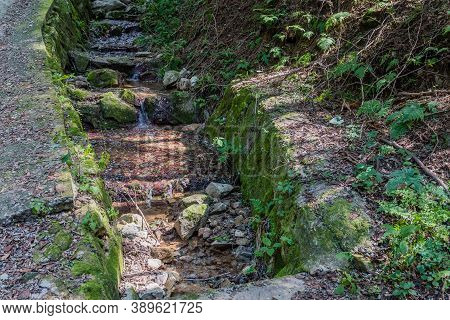 Stream Of Water Running Down Man Made Drainage Ditch In Mountain Park.