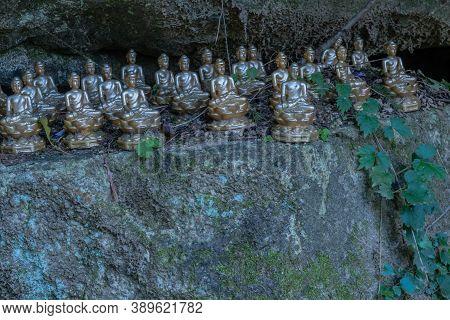 Miniature Sitting Buddhas On Ledge Of Boulder In Mountainous Public Park.