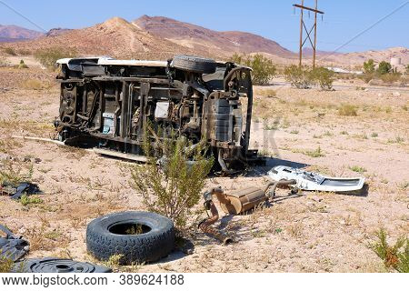 October 4, 2020 In Beatty, Nv:  Turned Over Car Surrounded By Auto Parts On An Arid Field Taken At A