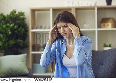 Young Stressed Woman Touching Temples With Hands And Feeling Bad