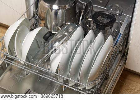 Dirty Dish In Open Integrated Dishwasher. Open Dishwasher With Dirty Dishes Inside Before Washing. F