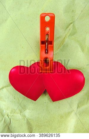 Two Hearts On A Clothespin Tied Together On Crumpled Craft Paper