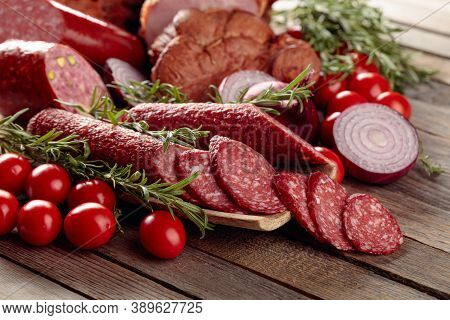 Food Tray With Delicious Salami, Ham, Fresh Sausages, Tomato, And Rosemary. Meat Platter With A Sele