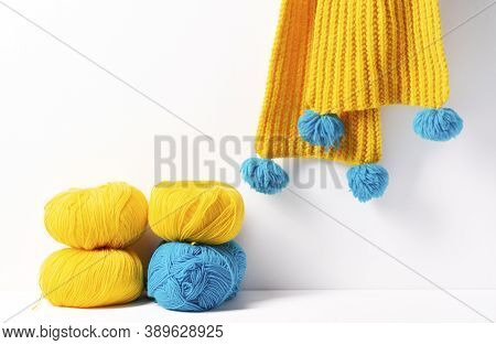 Skeins Of Yellow And Blue Yarn Lie On A White Background, With A Yellow Knitted Scarf Hanging In The