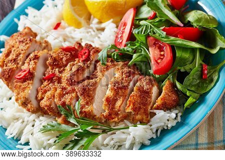 Chicken Cutlet Rice Bowl Served With Spinach Tomato Salad, Horizontal View From Above, Close-up