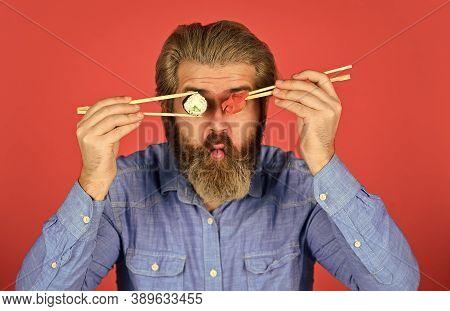 Man Eat Sushi Chopsticks. Sushi Rolls. Eastern Culture. Bearded Hipster Eating Rolls. Japanese Food