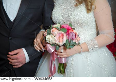 Close-up Photo Of Bride Standing Next To Her Husband Holds A Bouquet In Her Hand Outdoor . Nice Wedd