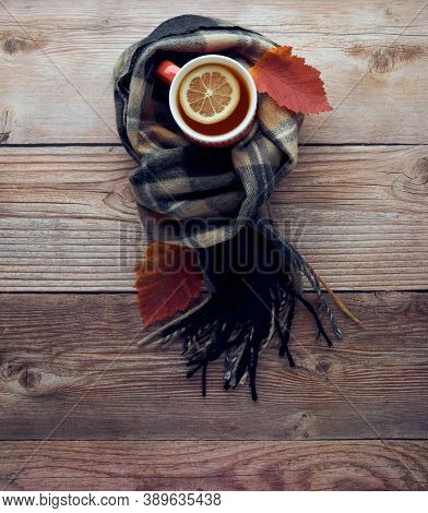 Autumn Leaves, Cup Of Black Tea With Lemon Slice And Warm Scarf On Wooden Table. Fall Season, Leisur