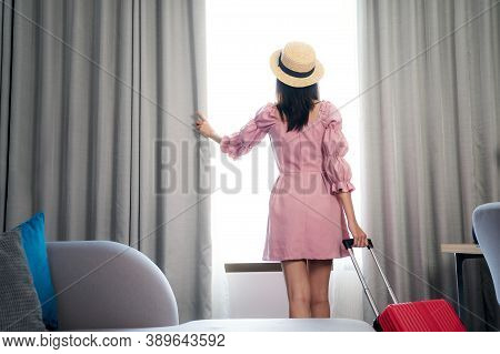 Asian Woman Traveller In Pink Dress Arrive To Room In Hotel And Open Curtain For Enjoy With Outside