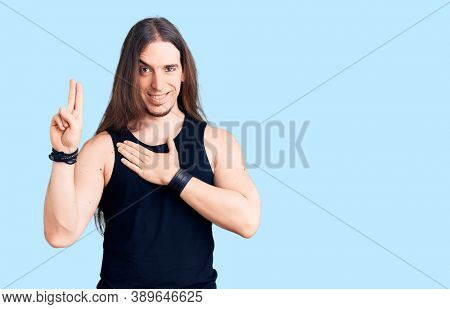 Young adult man with long hair wearing goth style with black clothes smiling swearing with hand on chest and fingers up, making a loyalty promise oath