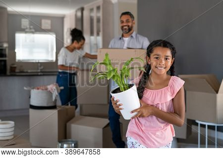 Happy smiling girl holding plant in new home while indian father watching her. Portrait of cute multiethnic daughter feeling excited in new house while looking at camera.