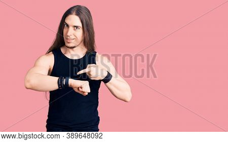 Young adult man with long hair wearing goth style with black clothes in hurry pointing to watch time, impatience, upset and angry for deadline delay