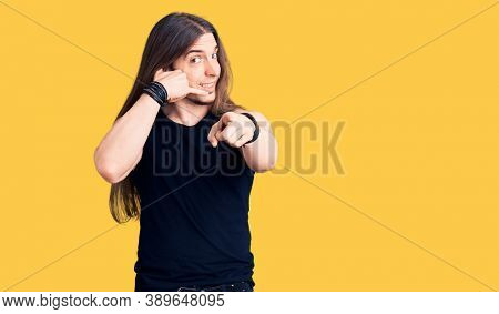 Young adult man with long hair wearing goth style with black clothes smiling doing talking on the telephone gesture and pointing to you. call me.