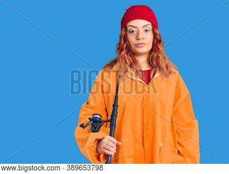 Young latin woman wearing fisher raicoat holding rod thinking attitude and sober expression looking self confident