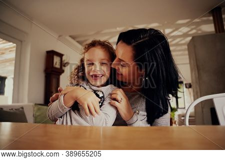 Portrait Of Cheerful Mother Tickling And Kissing Daughter Sitting On Chair At Home