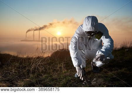 Crouched Environmentalist Working Outdoors On The Hill Collecting Samples For His Study, Smoking Pip