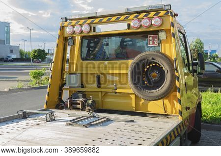 Warsaw, Poland - July 29, 2020: Yellow Car Tow Truck In The Parking Lot. Car Tow Truck For Small And