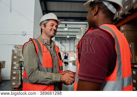 Smiling Caucasian Factory Male Shaking Hands With Co-worker Making Business Deal In Warehouse