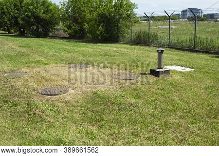 Metal Sewer Manholes On Green Grass. Four Sewer Hatches With An Exhaust Hood Near The Security Facil