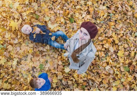 Tired Mother Walks With Children In Autumn Park. Mom And Two Sons On Fall Leaves Background. Top Vie