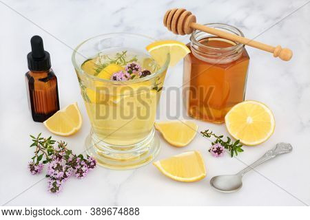 Alternative medicinal remedy for cold & flu virus with thyme herb, honey & lemon in glass with essential oil. Immune boosting medication, is anti bacterial, antiseptic and anti viral. On marble.