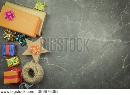 Wrapping Gifts With Hands In Gift Paper On The Table As A Background. Birthday Or Anniversary Gifts