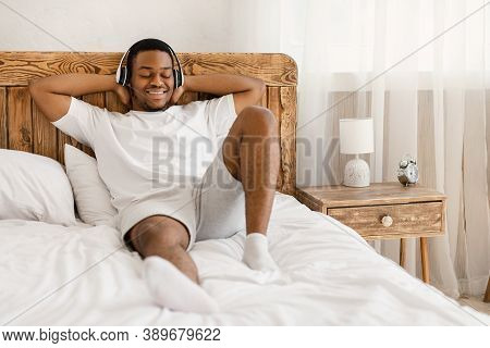 Relaxed African American Man Listening To Music In Wireless Earphones, Enjoying Relaxing Songs Playl