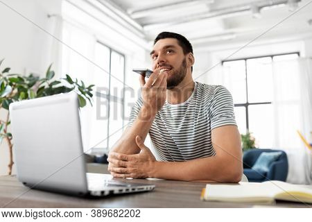 technology, remote job and people concept - happy smiling man with laptop computer calling on smartphone or using voice command recorder at home office