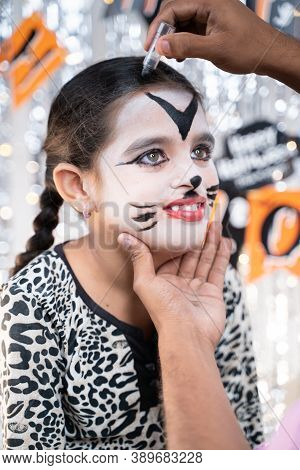 Parent Helping Her Daughter To Get Ready For Halloween By Doing Make-up - Concept Of Halloween, Holi