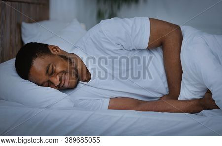 Abdominal Pain. Black Guy Suffering Stomachache Touching Aching Abdomen Lying In Bed At Home At Nigh