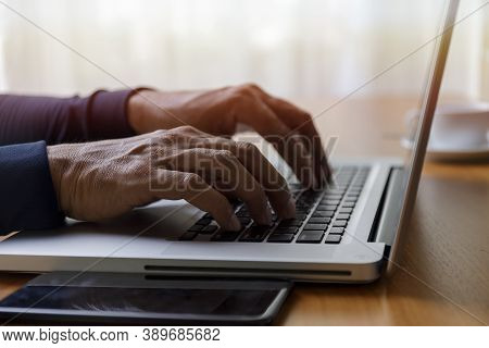 Close Up Businessman Using Laptop Computer At Home. Close Up Male Hands Typing On Laptop Keyboard In
