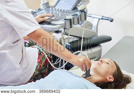 Woman Patient During The Ultrasound Examination Of A Thyroid Lying On The Couch In Medical Office. G