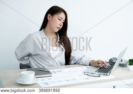 Asian Women Are Tired From Work On Laptop Sits In A Chair Stretching To Relax And Unwind While Worki