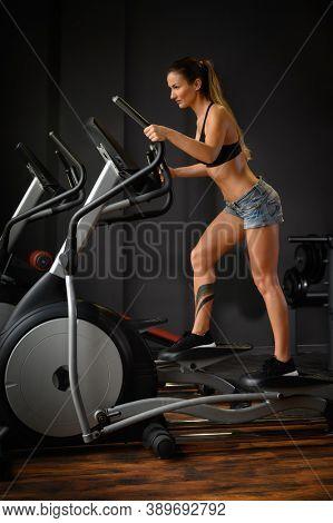 Cute sportive brunette woman exercising using elliptical cross trainer machine in dark gym interior with black walls