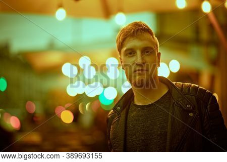 Evening life in a big city. Modern young man walks along a city street lit by evening lights.