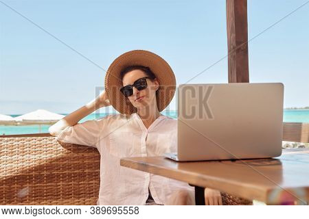 Young Woman Using Laptop Computer On A Beach. Freelance Work Concept.\rpretty Young Woman Using Lapt