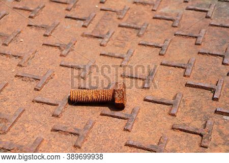 Rusty Metal Bolt Lay Down On The Steel Plate Floor In Brown Color With Rusty Iron. Rust Is A Reddish
