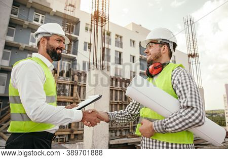 Low Angle Side View Of Positive Male Inspector And Foreman With Papers Shaking Hands While Having Me