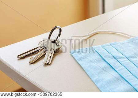 Medical Face Mask And Set Of Three House Keys On The Ring Over A Table In A Room. Personal Protectio