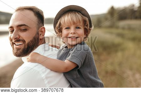 Cheerful Bearded Man Giving Piggyback Ride To Cute Blond Boy While Resting On Lake Shore Together