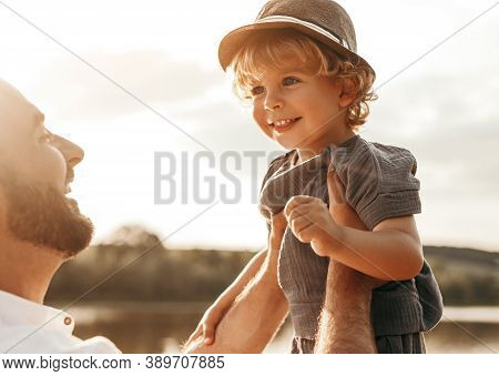 Side View Of Loving Dad Holding Adorable Curly Haired Little Son On Hands While Playing Together And