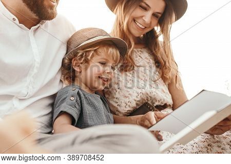 Low Angle Of Delighted Boy Reading Fairytale With Crop Mother And Father During Picnic In Countrysid