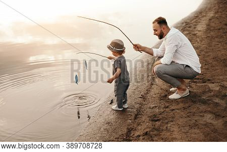 High Angle Of Bearded Man Teaching Boy To Catch Fish While Playing On Lake Shore Together