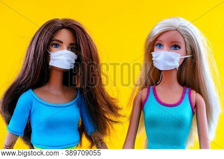 Tambov, Russian Federation - June 12, 2020 Two Barbie Dolls With Medical Masks Against Yellow Backgr