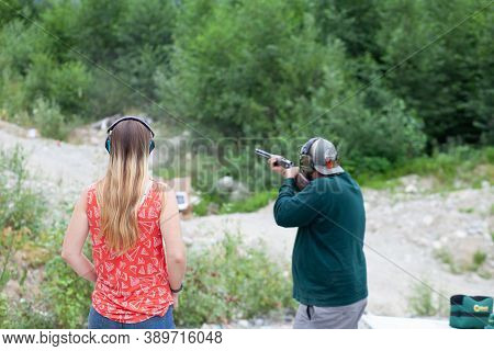 A Young Women Stands Behind A Man Holding A Shotgun Downrange, Shooting Clay Pigeons To Practice Aim