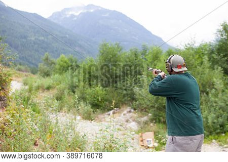 A Man Holds A Shotgun Downrange Ready To Fire At A Clay Pigeon To Practice His Aim In Squamish, Brit