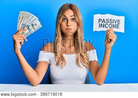 Beautiful blonde young woman holding dollars and passive income text puffing cheeks with funny face. mouth inflated with air, catching air.
