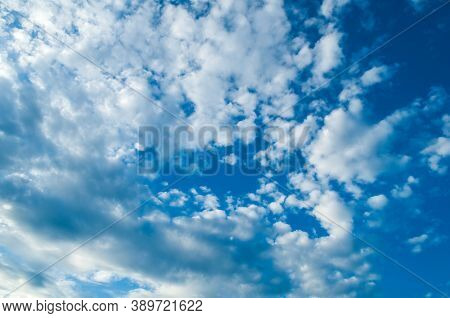 Blue sky background, white dramatic fluffy sky clouds lit by sunset light. Vast sky landscape scene, blue sky natural view. Sky landscape. Blue sky background, vast sky landscape, sky scene with dramatic clouds